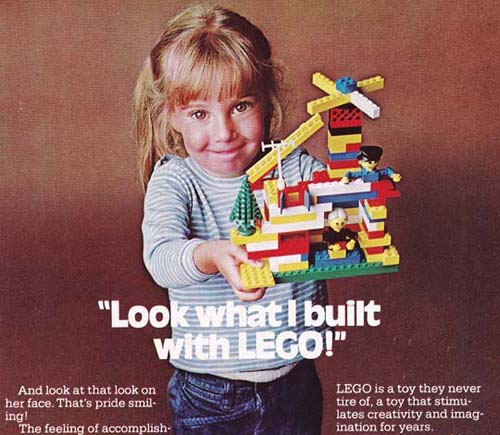 "A girl holds up a chaotic lego set. Text across the image reads ""Look what I built with LEGO."" Smaller text reads ""And look at that look on her face. That's pride smiling"" and ""LEGO is a toy they never tire of, a toy that stimulates creativity and imagination for years."""