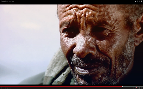 A black man with graying beard and dramatically wrinkled face looks past the viewer.