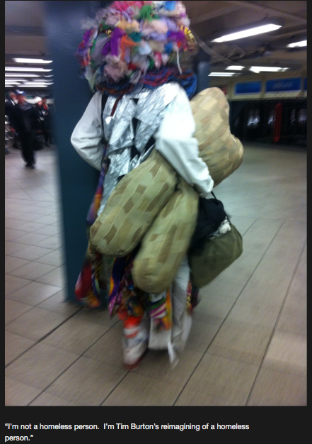 "A photograph of a person in clownish garb holding a stuffed toy that is vaguely shaped like a human chromosome. He/she is wearing a giant bulbous wig made of colored pieces of fabric. The caption provided says ""I'm not a homeless person. I'm Tim Burton's reimagining of a homeless person."""