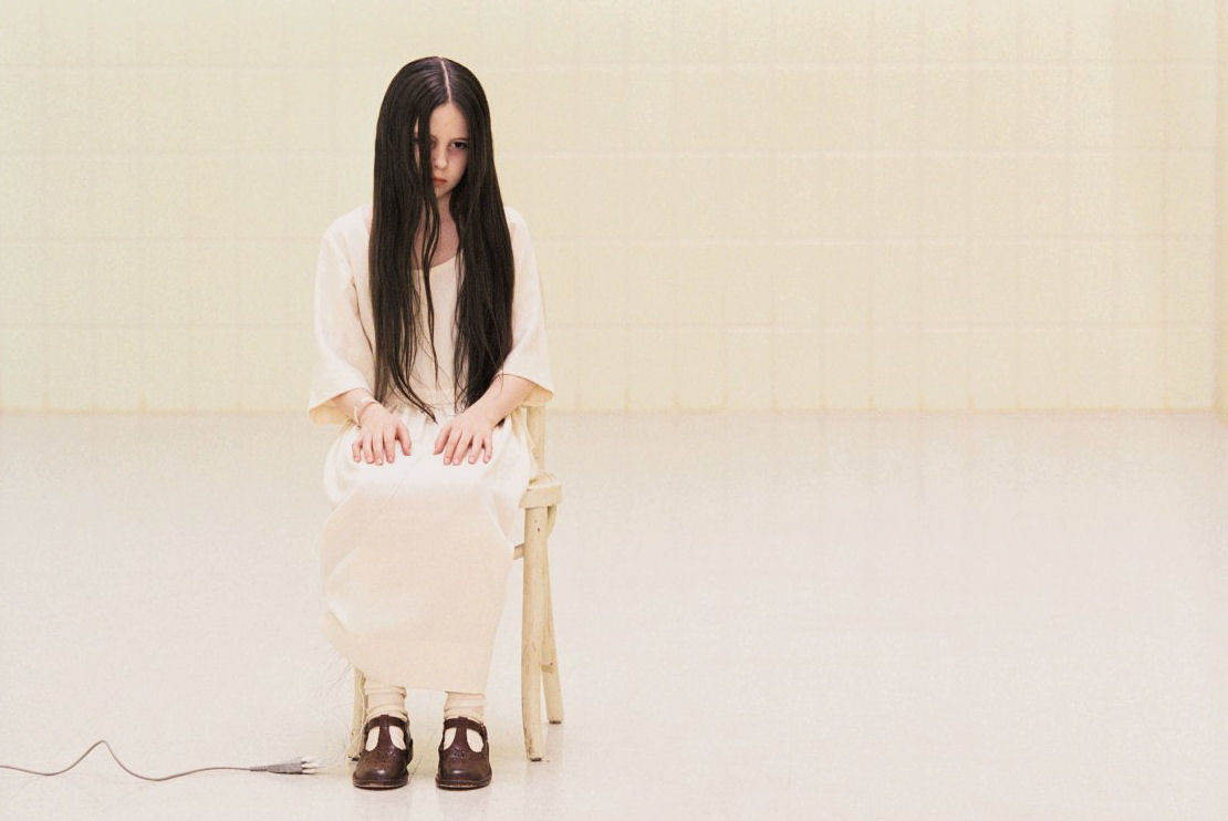 Samara from The Ring sitting in a psychiatric ward, hooked up to wires
