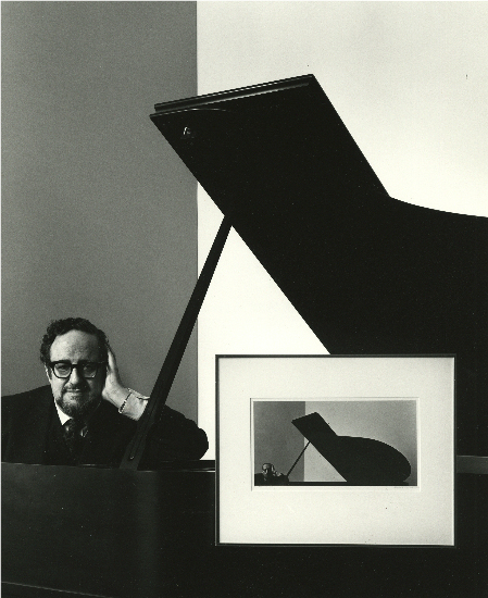 Arnold Newman self portrait, posed next to a piano and his framed portrait of Igor Stravinsky