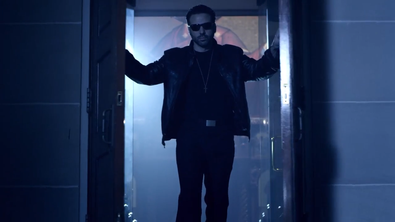 Image of Jamie Casino opening double wooden doors to a church, standing between them, while wearing a leather jacket and sunglasses.