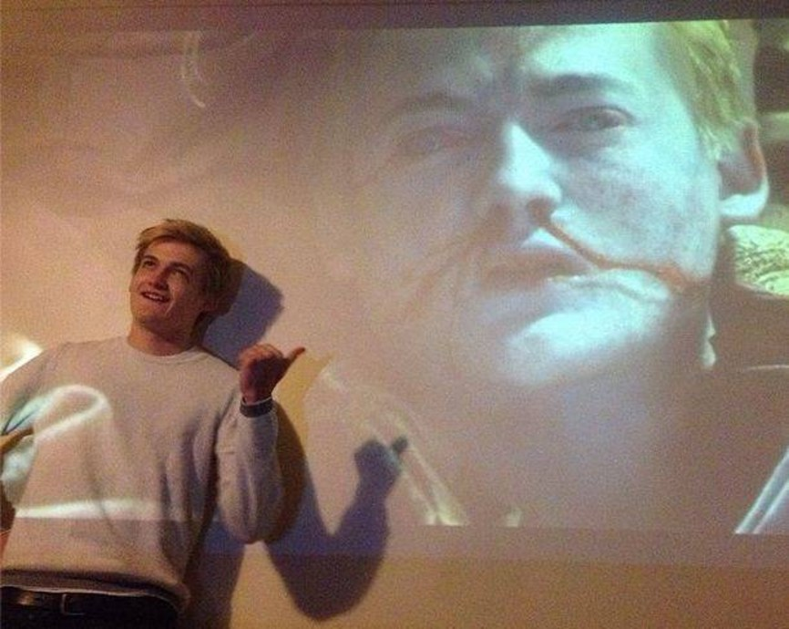 Picture of Jack Gleeson standing in front of a screen, on which Joffrey Baratheon (played by Gleeson) is shown dead, blood streaming from his nose