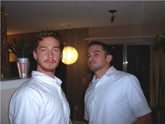 Picture of celebrity Shia LaBeouf posed next to an unknown black-haired white man.  The two are posed in the middle of a house; LaBeouf is on the left and the other man on the right of the shot.