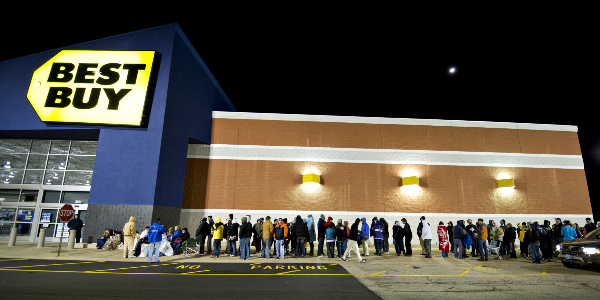 A line of people wait outside of Best Buy for the store to open