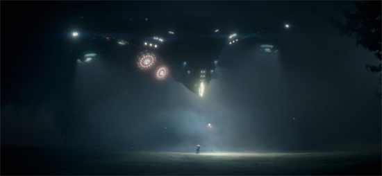 A spaceship whose sleek black body and glowing lights evokes classic Steven Spielberg films abducts the future Starlord.