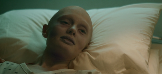 Quill's mother, resting on a pillow in the hospital. The scene is subtly tinted gold.