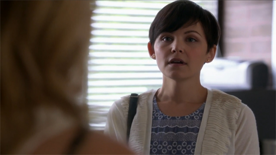 Mary Margaret, a character from Lost, stares at the camera. She wears a blue patterned dress beneath a thin white sweater jacket.