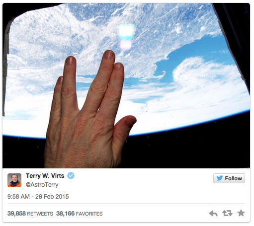A hand makes the Live Long and Prosper sign against a window of the International Space Station.