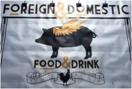 Photo shows exterior of the restaurant Foreign & Domestic, which features a pig with wings.