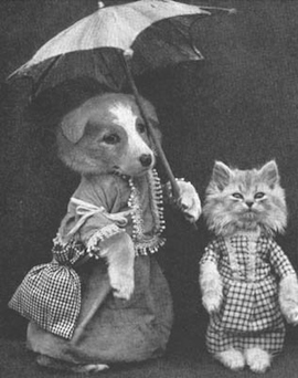 black and white photo of a dog and cat in turn of the century clothing